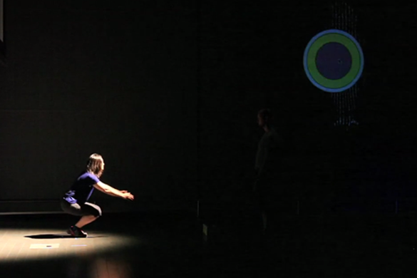 The sphere changes color and position based on the performer's movements.